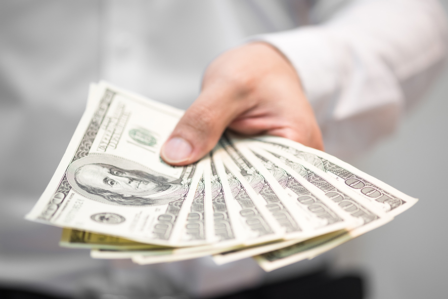 Businessman holding money on hand, Spreading one hundred US Dollar bills.