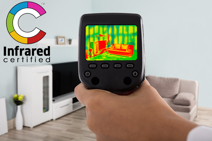 Person Hand Using Infrared Thermal Camera In Living Room. Infrared Certified logo in the corner of image.