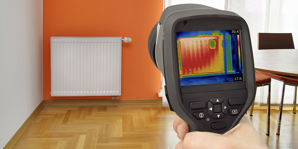 Hand holding a thermal imaging camera, detecting heat loss in central heating radiator.
