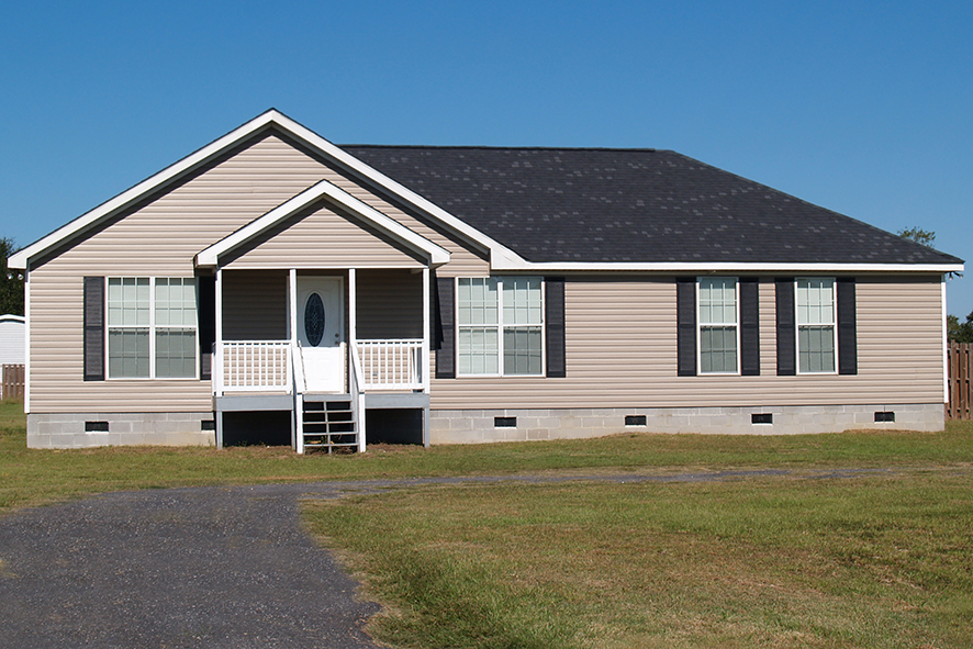 A manufactured home with blue sky and green grass.