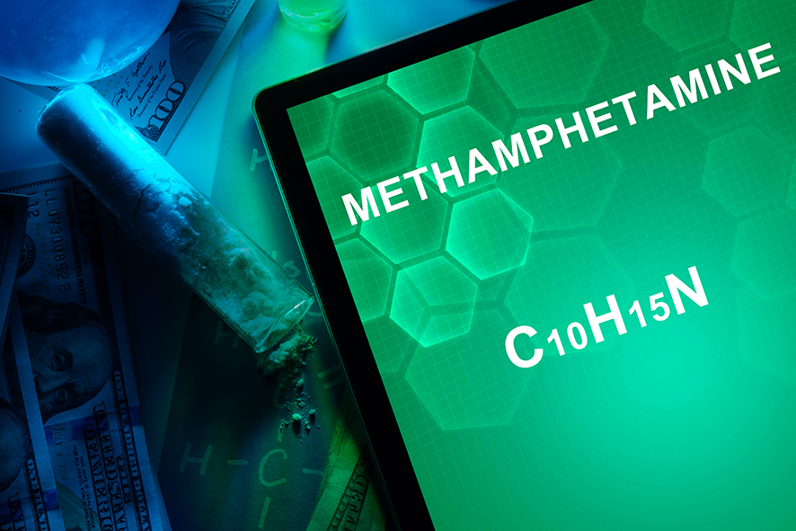"Tablet screen displaying the word ""Methamphetamine"" on a green background."
