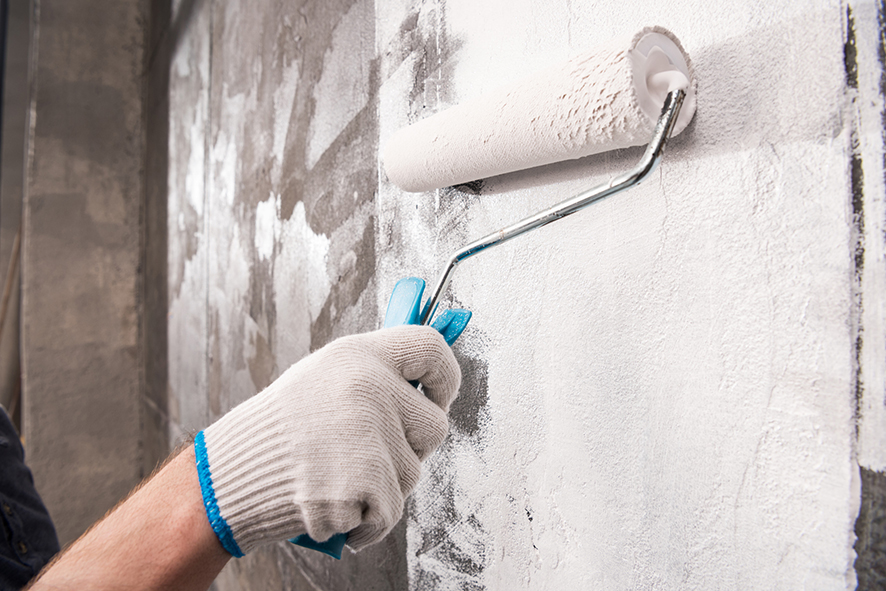 Hand with work glove painting a concrete wall with white paint and a roller brush.